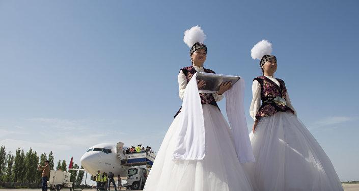 Девушки в национальных костюмах встречают гостей в международном аэропорту Манас. Архивное фото