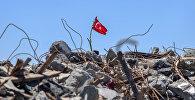 Флаг турецкой республики на развалинах снесенных при реконструкции площади Таксим строений. Архивное фото