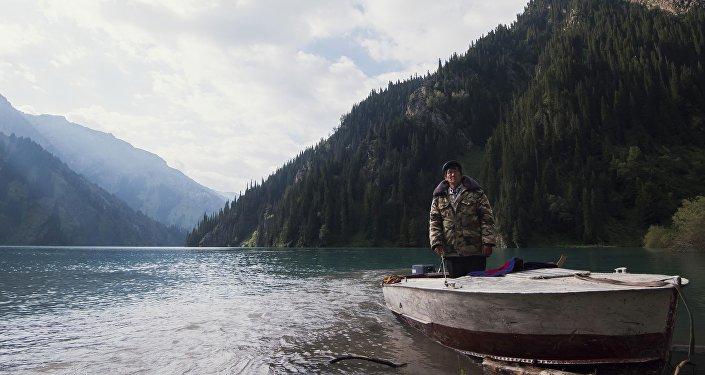 Сотрудник Сары-Челекского государственного биосферного заповедника проезжает на катере на озере. Архивное фото