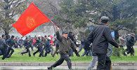Участник антиправительственного протеста в Бишкеке 7 апреля 2010 года с флагом Кыргызской Республики