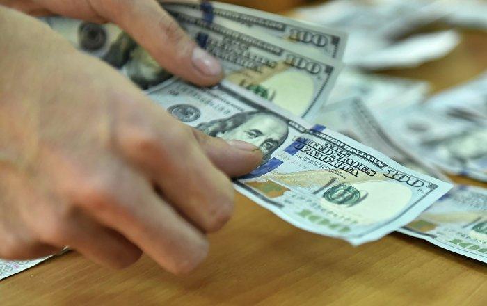 Долларовые купюры в руках мужчины. Архивное фото