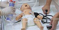 Сотрудники обучающего симуляционного центра демонстрируют симулятор новорожденного.
