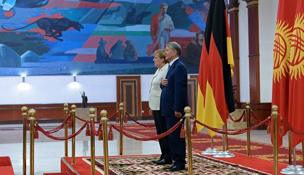 Эки мамлекеттин гимндери ойнолуп жаткан учур. Германиянын федералдык канцлери Ангела Меркель менен КР президенти Алмазбек Атамбаев