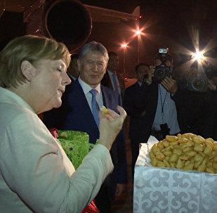 Ангела Меркелди аба майдандан кучак толо гүл жана боорсок менен тосуп алышты