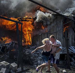 Жители станицы Луганской, которые спасаются от пожара, возникшего в результате авиаудара вооруженных сил Украины