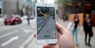 Мужчина играет в приложение Pokemon Go на телефоне. Архивное фото