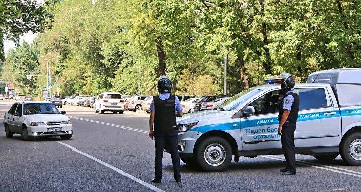 Полицейские дежурят на улицах Алматы после перестрелки.