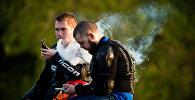 Молодые люди курят электронные сигареты. Архивное фото