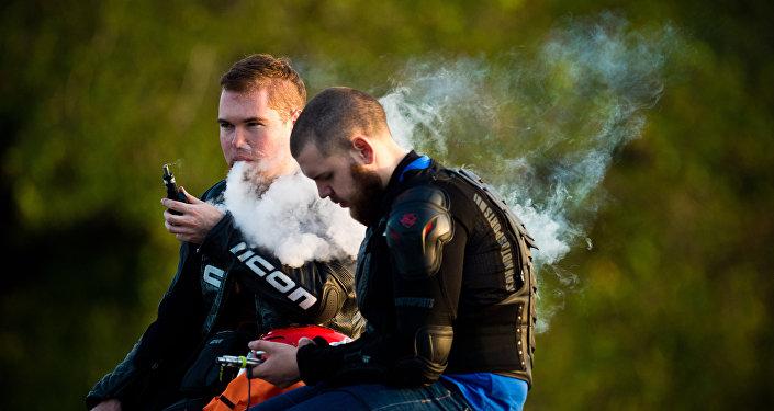 Архивное фото молодых людей, курящие электронные сигареты