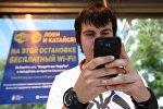 Молодой человек на остановке общественного транспорта, оборудованной бесплатным Wi-Fi. Архивное фото