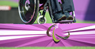 Спортсмен в инвалидной коляске и эмблема Паралимпиады. Архивное фото