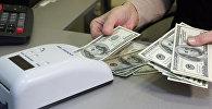 Проверка долларов на подлинность в пункте обмены валюты. Архивное фото