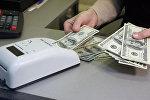 Архивное фото кассира пересчитывающего доллары США