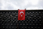Люди с турецким флагом на здании в Стамбуле. Архивное фото