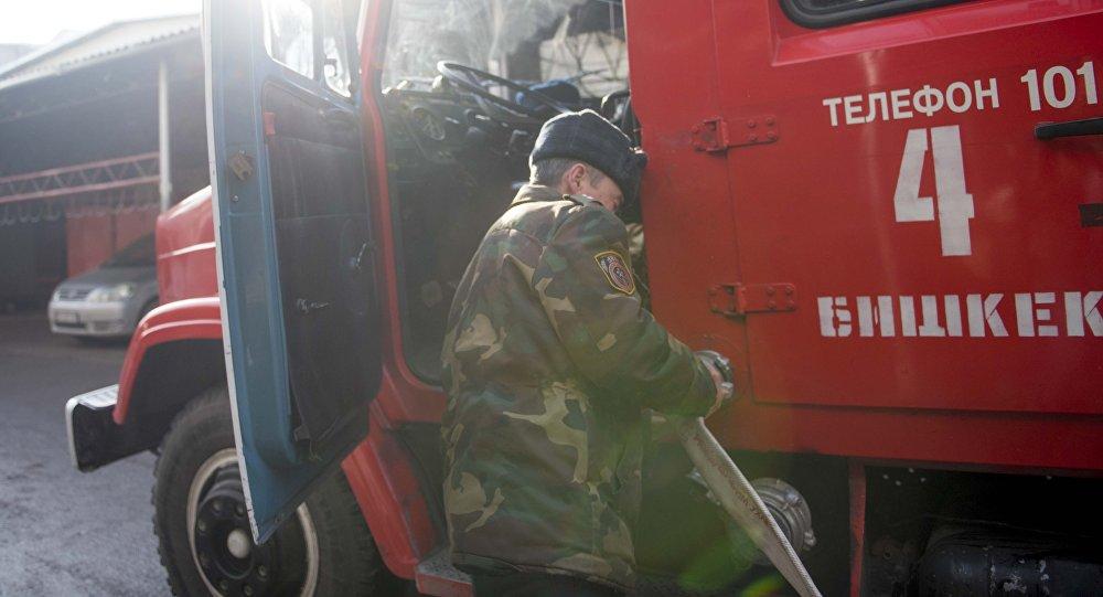 Сотрудник МЧС Кыргызстана у пожарной машины. Архивное фото
