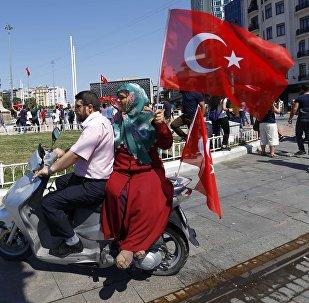 Женщина держит турецкий флаг, сидя на скутере возле площади Таксим в Стамбуле, Турция. Архивное фото