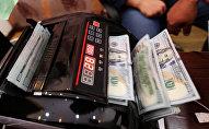 Счетная машина пересчитывает доллары США. Архивное фото