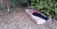 Мужчина без определенного места жительства (бомж) спит на матраце в центре столицы