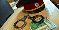 Милицейская фуражка с деньгами и с наручниками. Архивное фото