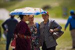 Женщины укрываются зонтом от солнца. Архивное фото