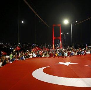 Проправительственные демонстранты держат гигантский турецкий флаг во время марша через Босфорский мост в Стамбуле, Турция. Архивное фото