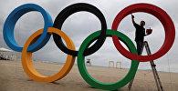 Человек раскрашивает олимпийские кольца. Архивное фото