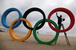 Человек раскрашивает олимпийские кольца в Рио-де-Жанейро. Архивное фото