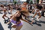 Танцовщицы в бикини выступают во время флешмоба на площади перед станцией Синдзюку в Токио