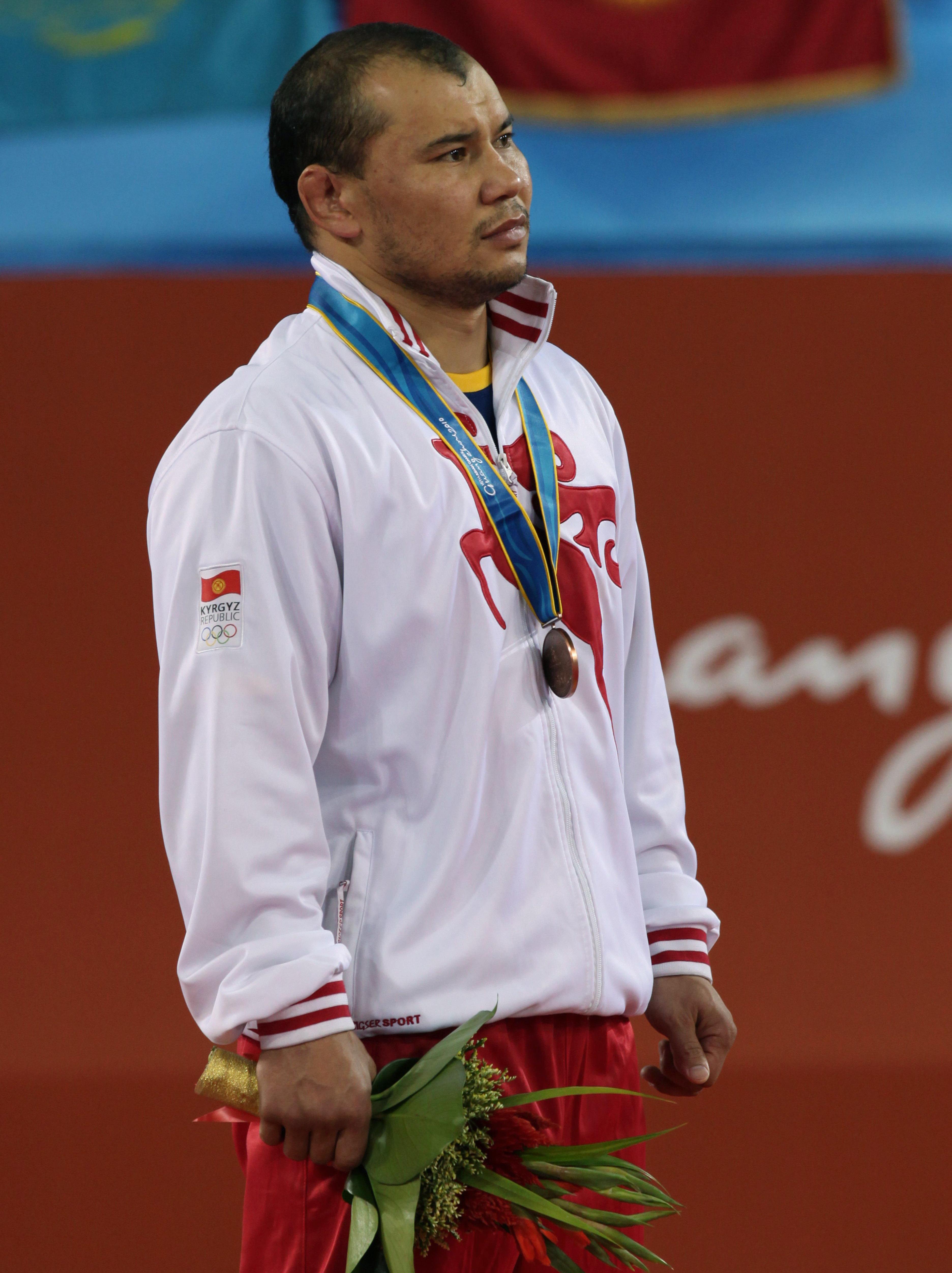Бронзовый призер из Кыргызстана Жанарбек Кенжеев во время церемонии награждения среди мужчин по греко-римской борьбе на XVI Азиатских играх в Гуанчжоу. 22 ноября 2010 года