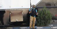Вооруженный человек стоит у захваченного здания полка патрульно-постовой службы