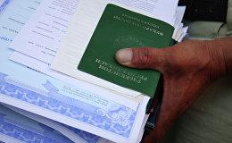 Мужчина держит документы мигрантов. Архвное фото
