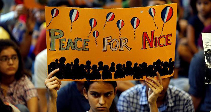 Девушка держит плакат во время молитвы в память погибшим теракта в Ницце