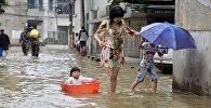 Женщина с детьми во время наводнения в Китае. Архивное фото