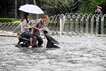 Мужчина и женщина едут на скутере во время наводнения в Пекине. Архивное фото
