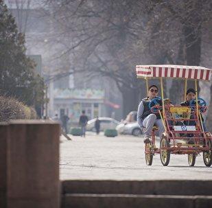 Горожане на четырехколесном велосипеде на улицах города Бишкек. Архивное фото