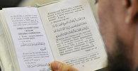 Куран китебин окуп жаткан адамдын архивдик сүрөтү
