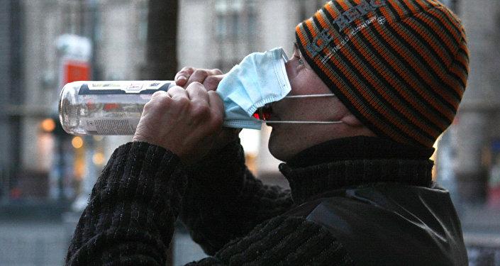 Мужчина в защитной маске пьет водку. Архивное фото