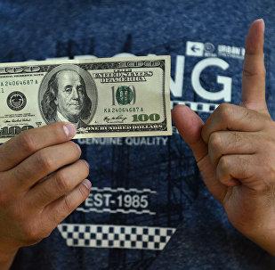 Сто долларовая купюра в руках мужчины. Архивное фото