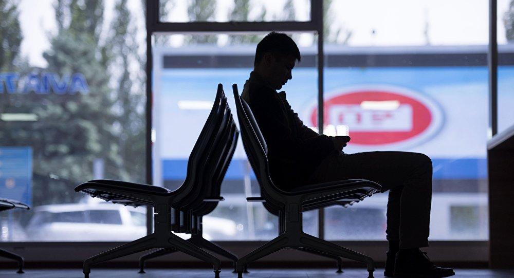 Аэропортто күтүүчү залда отурган жүргүнчү. Архивдик сүрөт