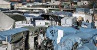 Мигранты за пределами палаток в самом большом нелегальном лагере вдоль северного побережья Франции, в портовом городе Кале. Архивное фото