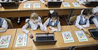 Ноутбук менен окуган окуучулар. Архивдик сүрөт