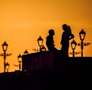 Пара разговаривают на закате. Архивное фото
