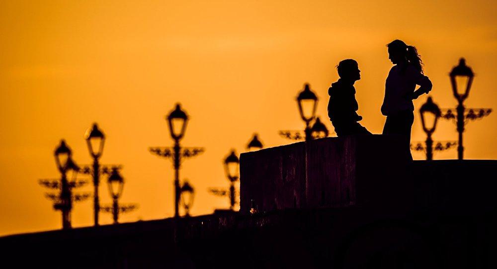 Архивное фото молодых людей, которые разговаривают на закате