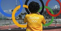 Мужчина у олимпийских колец в Олимпийском парке в Рио-де-Жанейро. Архивное фото