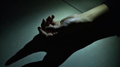 Рука молодого мужчины на полу. Архивное фото