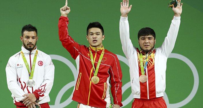 Обладатель серебряной медали турецкий спортсмен Данияр Исмаилов (слева), золотой медали китайский тяжелоатлет Ши Чжиюн и бронзы кыргызстанец Иззат Артыков во время церемонии награждения