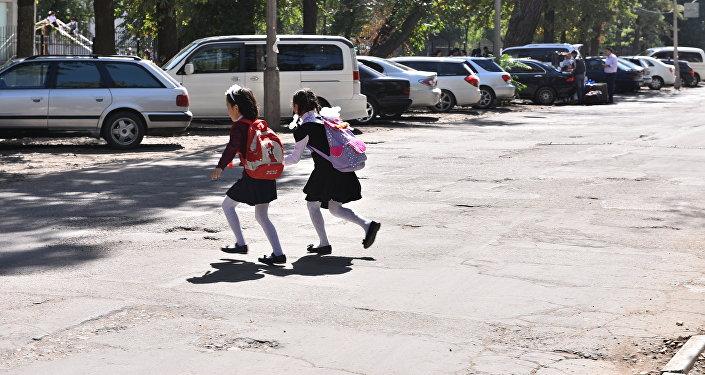 Школьницы перебегают через улицу в Бишкеке. Архивное фото