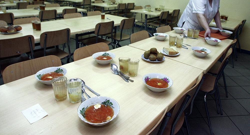 Работник столовой-пекарни в средней школе разносит обеды. Архивное фото