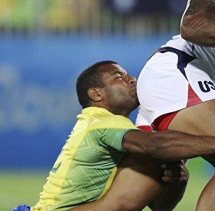 Игрок сборной Бразилии Андре Насименто держится за спортсмена из США во время регби на XXXI летних Олимпийских играх в Рио-де-Жанейро