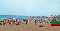 Люди отдыхают на пляже озера Иссыккуль. Архивное фото